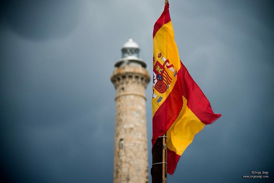 Spanish flag and the Cabo de Palos lighthouse in the background