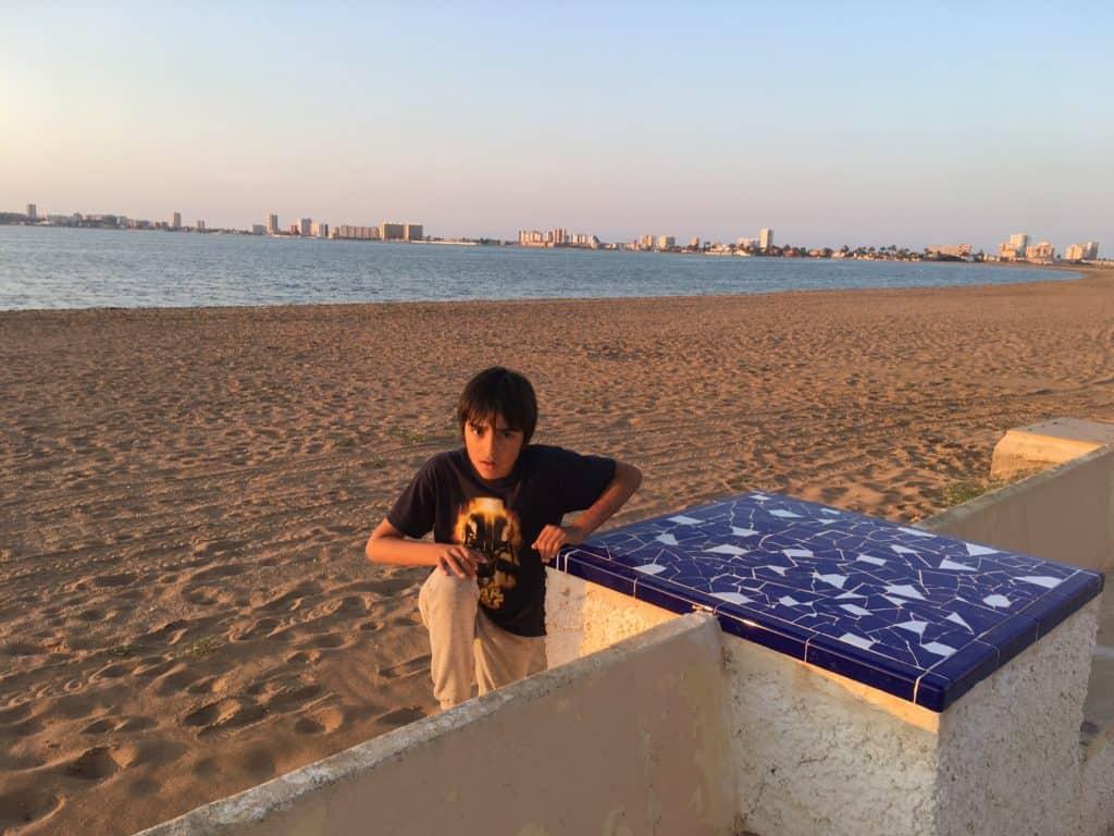 Niño en el paseo marítimo junto a la playa